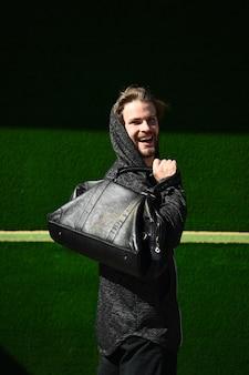 Sportif fort posant en plein air avec un sac en cuir de sport sur fond vert, homme heureux sportif de remise en forme en sweat à capuche avec visage barbu souriant, mode sportive, sentiments et émotions, mode de vie sain