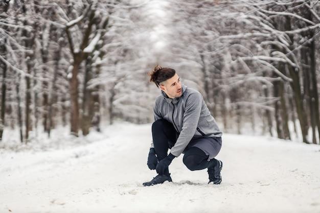 Sportif à genoux et attachant les lacets au jour d'hiver enneigé en forêt. vêtements de sport, mode de vie sain, fitness hivernal