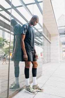 Sportif jeune athlète jeune homme debout contre le miroir