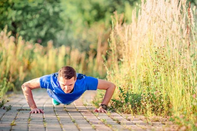 Sportif jeune homme faisant des exercices de sport en plein air dans le parc