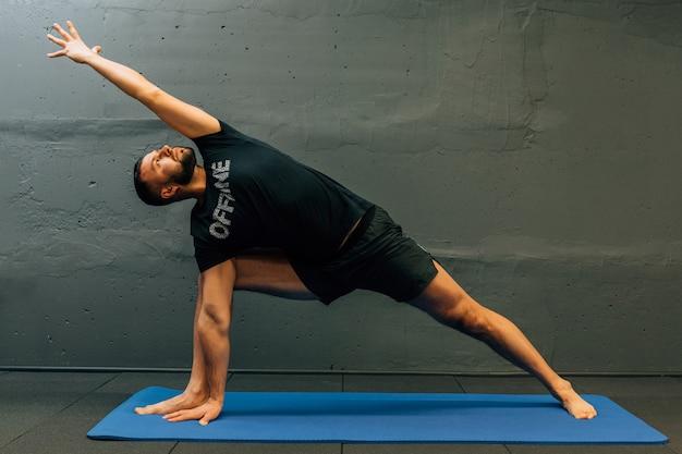 Sportif jeune homme travaillant, faisant du yoga appui renversé.