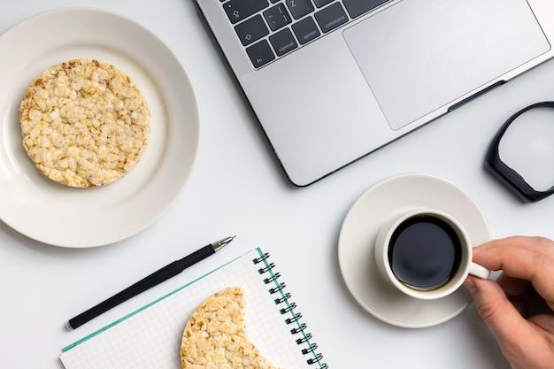 Sportif mangeant du riz croustillant avec du café près de son ordinateur portable.