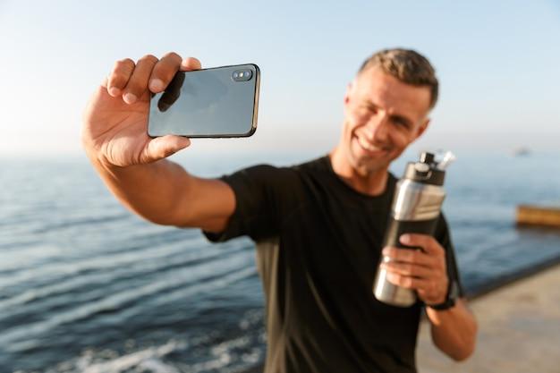 Sportif mature prendre un selfie avec une bouteille d'eau sur la plage.