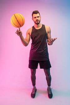 Sportif mécontent faisant tourner le ballon de basket-ball sur le doigt. vue de face du jeune joueur de basket-ball européen barbu regardant la caméra. isolé sur fond bleu et rose. prise de vue en studio