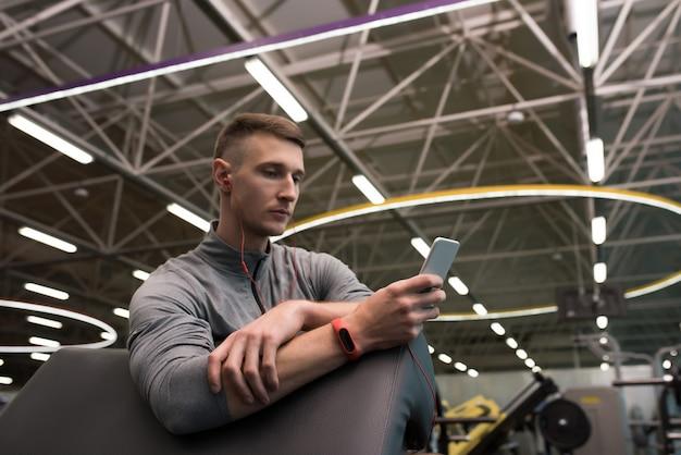 Sportif moderne utilisant un smartphone pendant la pause