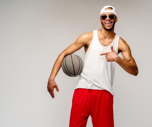 Sportif musclé jouant au basket-ball sur un mur gris clair