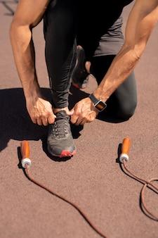 Sportif musclé en vêtements de sport noirs attachant les lacets sur sneaker avant de faire de l'exercice avec corde à sauter