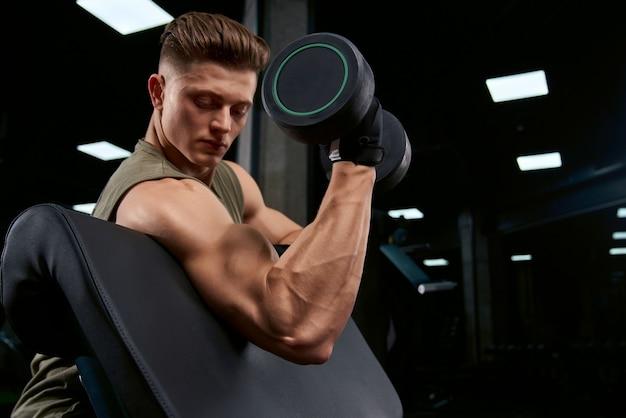 Sportif musculaire, construction de biceps avec haltère.