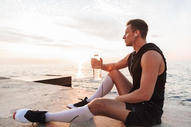 Sportif en plein air à la plage, écouter de la musique avec des écouteurs d'eau potable.