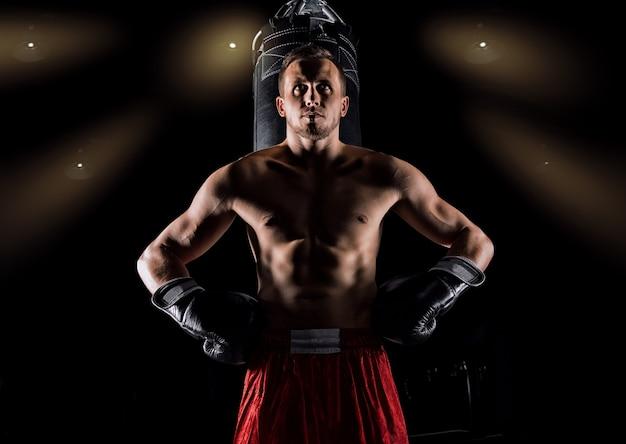 Un sportif professionnel d'arts martiaux mixtes se tient après le combat remporté près du sac et regarde d'un air menaçant son prochain adversaire.