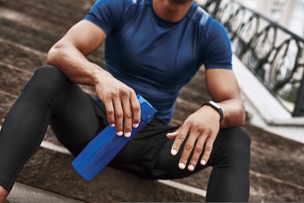 Un sportif recadré tient une bouteille d'eau alors qu'il est assis sur des marches avec l'extérieur