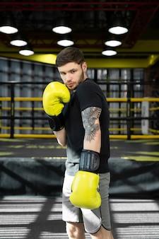 Sportif recueilli dans la salle de boxe pratiquant des coups de poing de boxe pendant l'entraînement