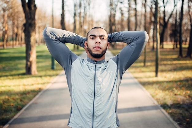 Sportif s'échauffant avant de courir dans le parc d'automne