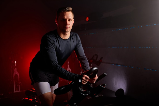 Sportif s'entraînant à l'équipement de sport dans le gymnase, un homme confiant et fort en survêtement a un entraînement intensif à vélo dans un club de fitness.