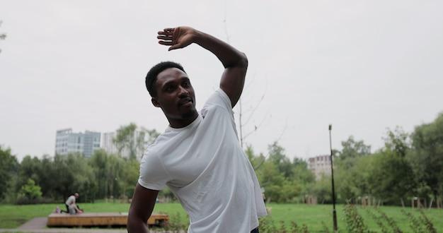 Sportif se préparant à une séance d'entraînement à l'extérieur dans le parc. homme afro-américain étirant les bras ou s'échauffant. concept de course saine et d'exercice en plein air.