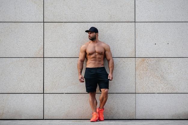 Un sportif sexy se tient topless près du mur. fitness, musculation.
