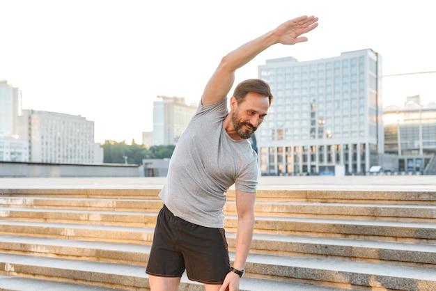 Sportif souriant, faire des exercices d'étirement