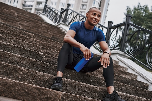Un sportif souriant tient une bouteille d'eau tout en étant assis sur des marches avec l'extérieur