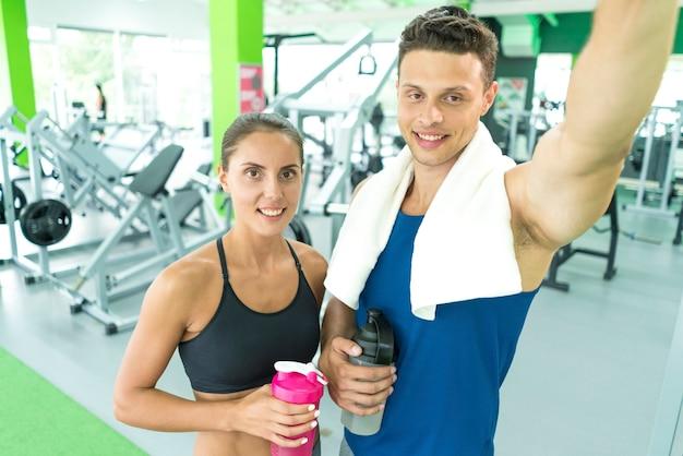 Le sportif et la sportive heureux font un selfie dans le centre sportif