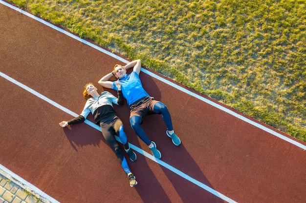 Sportif et sportive portant sur la piste de course en caoutchouc rouge d'un stade