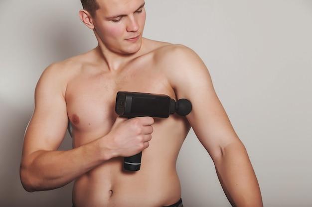 Le sportif tient un massage de choc au pistolet de sport dans le cabinet médical de la salle de sport. exercices de massage à domicile d'athlète. thérapie par percussion pour le massage régénérant du corps. concept de réadaptation des blessures. espace de copie