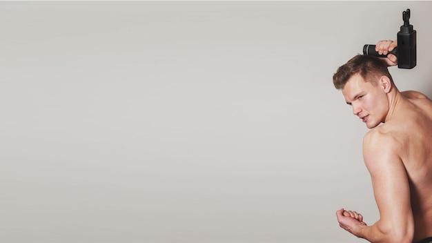Un sportif tient un massage de choc au pistolet de sport dans un cabinet médical de salle de sport