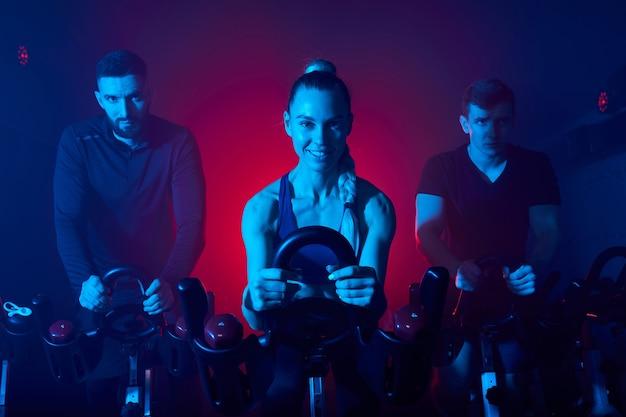 Les sportifs, faire du vélo d'exercice dans la salle de sport, profiter du temps d'entraînement, dans l'espace néon bleu fumé