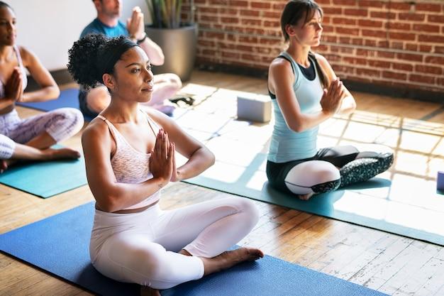 Les sportifs faisant une pose de sukhasana dans un studio