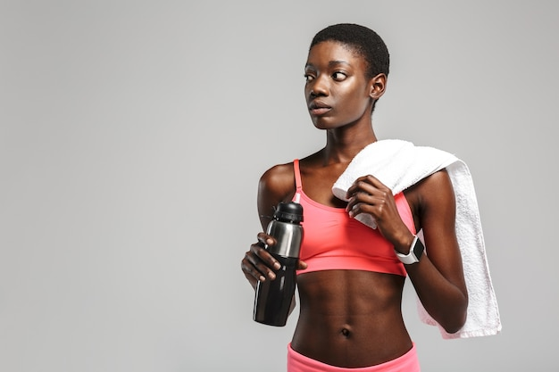Sportive afro-américaine avec de l'eau potable de serviette tout en travaillant isolé sur un mur blanc