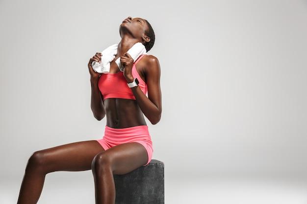 Sportive afro-américaine avec une serviette assise tout en faisant de l'exercice isolé sur un mur blanc