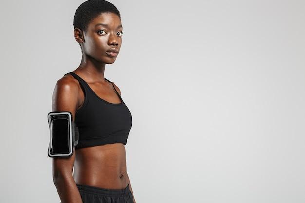 Sportive afro-américaine avec téléphone portable posant et regardant la caméra isolée sur mur blanc