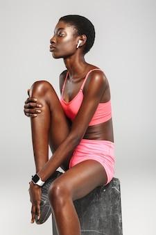 Sportive afro-américaine utilisant des écouteurs sans fil en position assise isolée sur un mur blanc