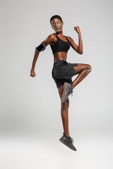 Sportive afro-américaine utilisant un téléphone portable et des écouteurs tout en faisant de l'exercice isolé sur un mur blanc