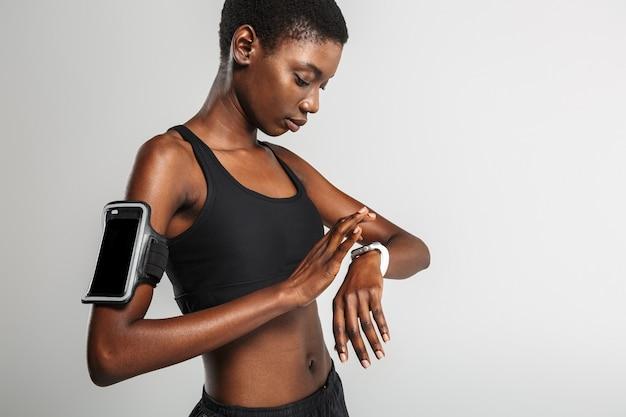 Sportive afro-américaine utilisant un téléphone portable et une montre intelligente tout en s'entraînant isolée sur un mur blanc