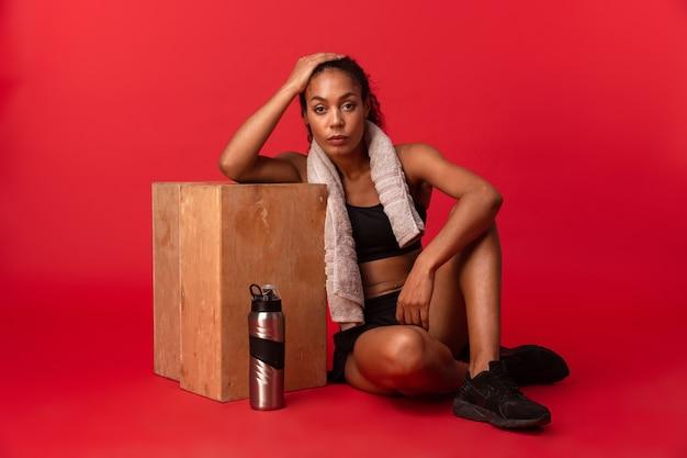 Sportive afro-américaine en vêtements de sport noir assis sur le sol avec une serviette et une bouteille d'eau, isolé sur mur rouge