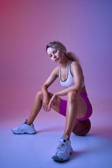 Sportive athlétique assise sur ballon en studio, fond néon. femme de remise en forme à la séance photo, concept sportif, motivation de style de vie actif