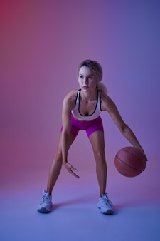 Sportive athlétique, exercice d'ajustement avec ballon en studio, fond néon