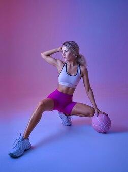 Sportive athlétique faisant de l'exercice avec ballon en studio, fond néon. femme de remise en forme à la séance photo, concept sportif, motivation de style de vie actif