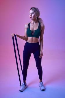 Sportive athlétique faisant de l'exercice avec du caoutchouc en studio, fond néon. femme de remise en forme à la séance photo, concept sportif, motivation de style de vie actif