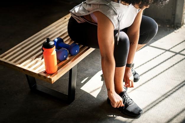 Sportive attachant ses lacets dans la salle de sport