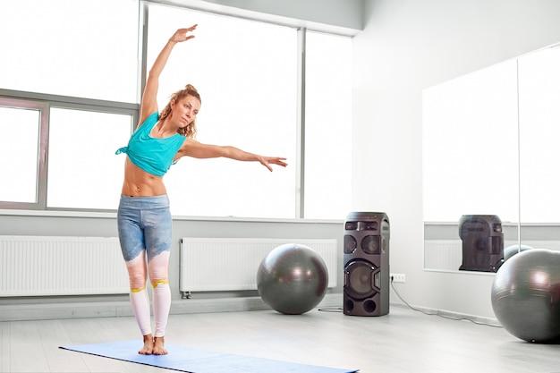 Sportive attrayante, faire des exercices sur le sol dans le studio des palais modernes belle fille sportive assouplir et étirer ses jambes et ses bras