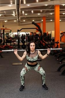 Sportive attrayante s'accroupit dans une salle de sport