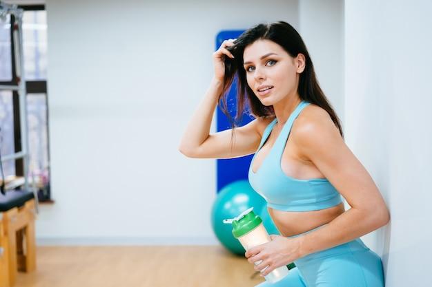 Sportive au repos et à boire de l'eau dans les escaliers de gym