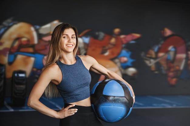 Sportive belle et motivée en tenue de sport, tenant un ballon de médecine à la taille et tenant la main sur la hanche.