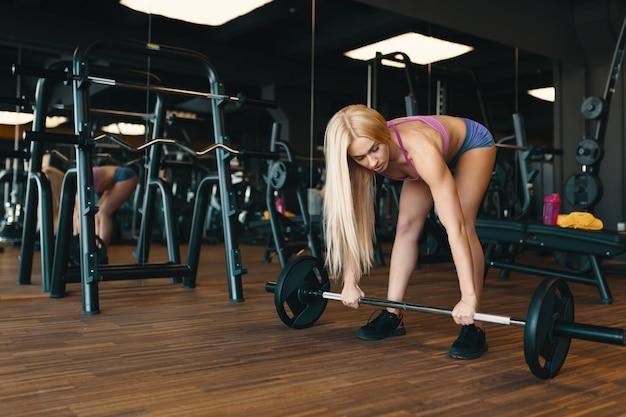 Sportive blonde en mini short soulevant des haltères à l'entraînement de gym