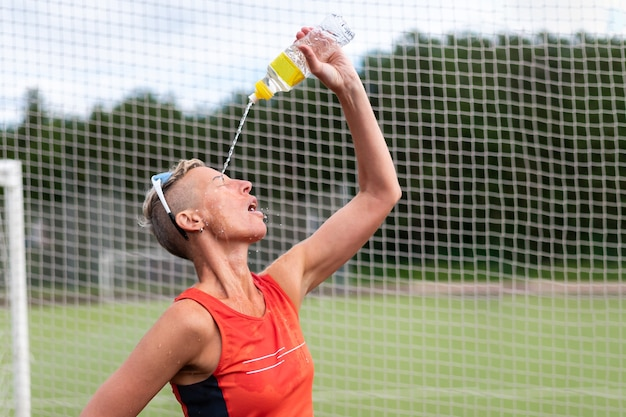 Une sportive boit de l'eau et lui verse de l'eau dessus. pour n'importe quel but.