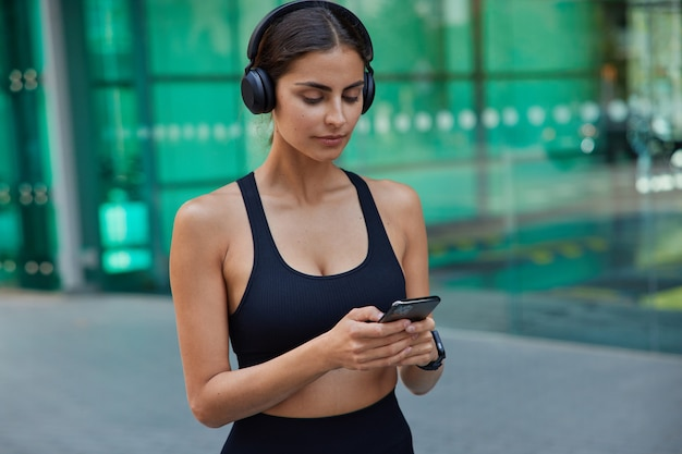 Une sportive brune sérieuse vêtue de messages texte de types haut recadrés écoute la piste audio dans les écouteurs a un entraînement de remise en forme flou