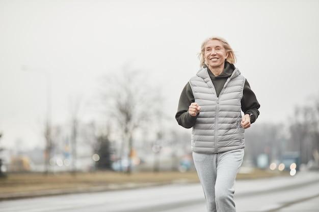 Sportive caucasienne senior énergique positive en gilet chaud et pantalon gris jogging le long de la route tout en s'entraînant en hiver