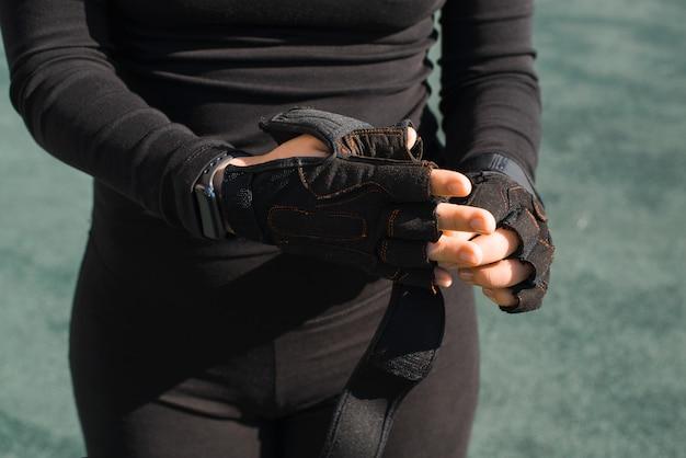 Sportive dans un ensemble de sport noir enlevant ses gants noirs en gros plan