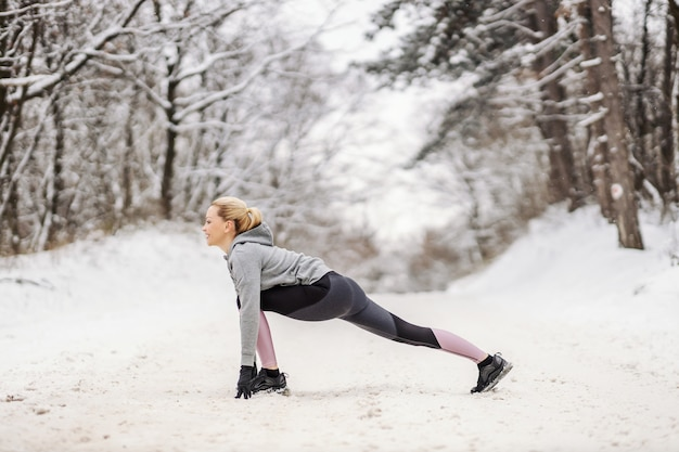 Sportive debout sur un chemin enneigé dans la nature en hiver et faisant des exercices d'étirement et d'échauffement. vie saine, fitness d'hiver, fitness en plein air